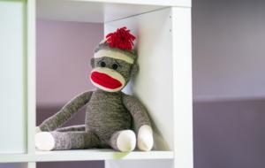sock monkey sitting on shelf in office