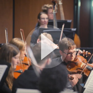 Northern State University students playing in orchestra with video play button